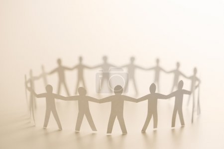 Photo for Cutout paper standing in circle holding hands. - Royalty Free Image
