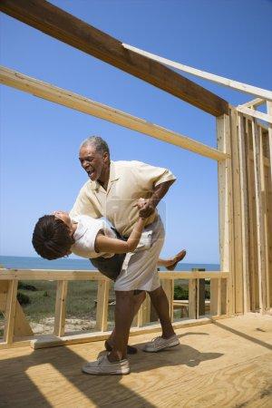 Photo pour Couple afro-américain d'âge moyen dansant dans la construction d'une nouvelle maison à la plage . - image libre de droit