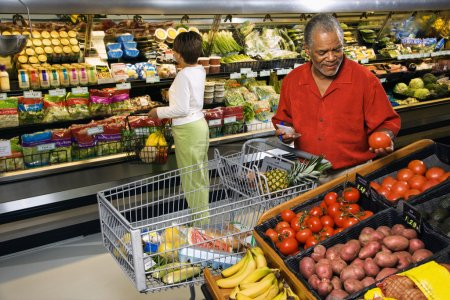 Photo for Middle aged African American man and woman in grocery store shopping for produce. - Royalty Free Image
