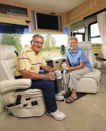Photo for Senior couple sitting in RV holding coffee cups and smiling. - Royalty Free Image
