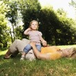 Caucasian mid adult woman lying in grass at park w...
