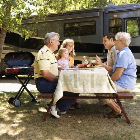 Foto de Familia caucásica tres generaciones sentado en la mesa de picnic frente hablando de vehículos recreativos. - Imagen libre de derechos