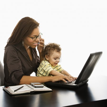 Photo for African American businesswoman at work on laptop and cell phone with toddler son on lap. - Royalty Free Image