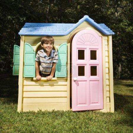 Boy in playhouse.