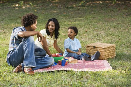 Photo for Smiling happy parents and son having picnic in park. - Royalty Free Image