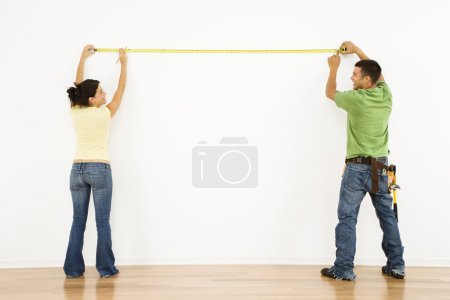 Couple measuring wall.