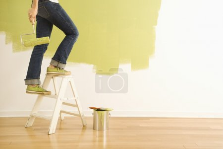 Woman painter on ladder.