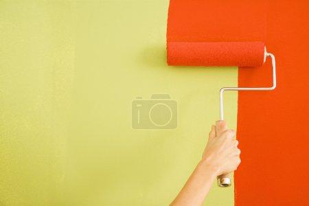 Photo pour Rouge peinture main féminine caucasien par-dessus un mur vert avec un rouleau à peinture - image libre de droit