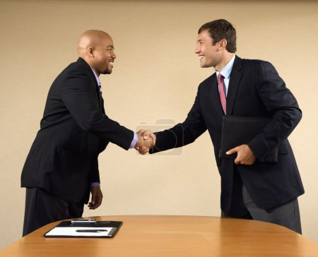 Photo for Two businessmen in suits shaking hands and smiling. - Royalty Free Image