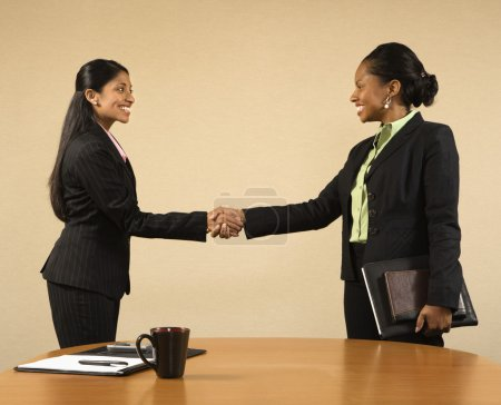 Two businesswomen in suits shaking hands and smili...