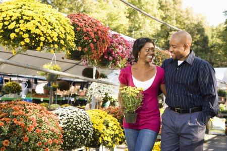 Photo pour Joyeux couple souriant cueillant des fleurs au marché aux plantes en plein air marchant et se tenant la main . - image libre de droit