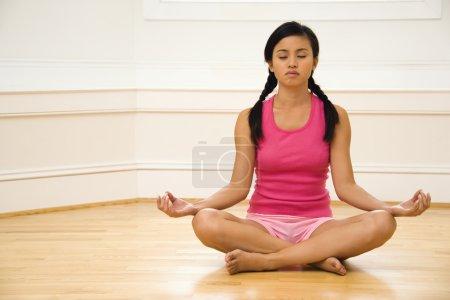 Photo pour Jeune femme assise sur plancher méditant dans yoga pose de lotus avec les jambes croisées et les yeux fermés. - image libre de droit