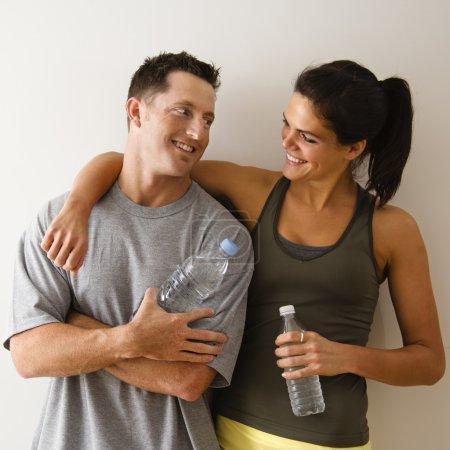 Foto de Hombre y mujer en el gimnasio en traje de fitness sosteniendo botellas de agua de pie contra la pared sonriendo el uno al otro . - Imagen libre de derechos
