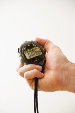 Hand holding stopwatch.