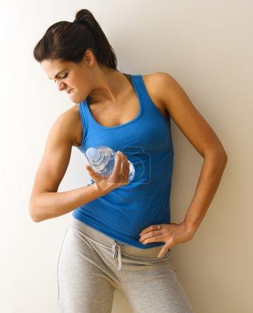 Photo pour Portrait de femme en tenue de fitness bras fléchissant muscle tenant bouteille d'eau . - image libre de droit