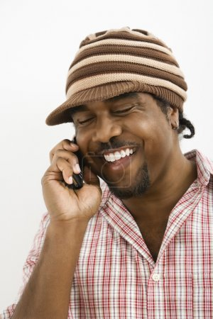 Photo for African-American mid-adult man wearing hat and smiling while talking on cell phone. - Royalty Free Image