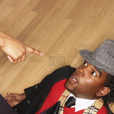 Foto de Hombre en parte posterior en un piso con mujer apuntando acusaciones - Imagen libre de derechos