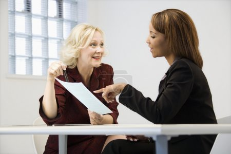 Photo for Businesswomen sitting at office desk going over paperwork pointing and smiling. - Royalty Free Image