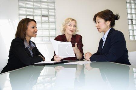 Photo pour Trois femmes d'affaires, assis au bureau de bureau ayant la paperasserie de rencontres et de débats sur. - image libre de droit