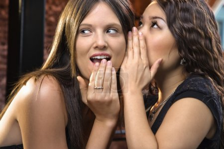 Photo for Attractive young woman whispering secret in friend's ear. - Royalty Free Image
