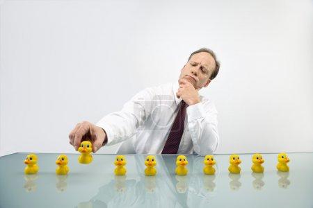 Photo pour Portrait d'un homme d'affaires caucasien d'âge moyen assis au bureau avec des canards dans une rangée . - image libre de droit