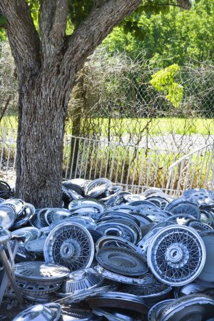 Stacks of hubcaps on ground.