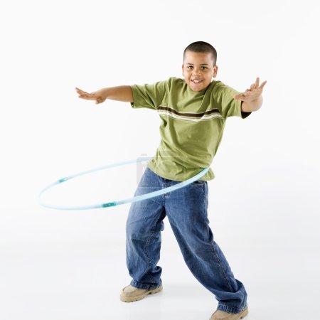 Boy using hula hoop.