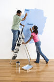 Couple painting wall blue.