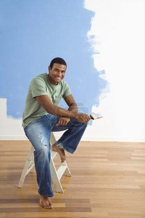Photo pour Jeune homme afro-américain assis à côté d'un mur à moitié peint avec pinceau . - image libre de droit