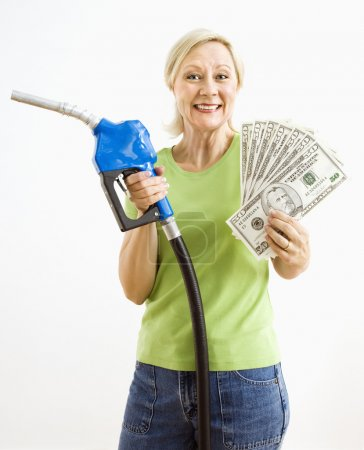Photo for Portrait of smiling adult blonde woman holding gas nozzle and lots of money. - Royalty Free Image