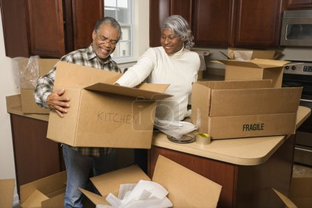Photo for Middle-aged African-American couple packing moving boxes in kitchen. - Royalty Free Image