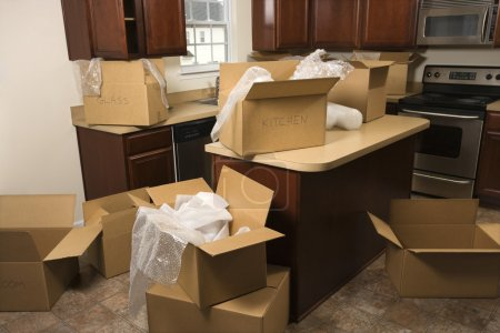 Photo for Cardboard moving boxes with bubble wrap in kitchen. - Royalty Free Image