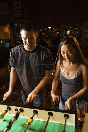 Couple playing foosball.