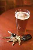 Glass of Beer and Keys on Bar Table