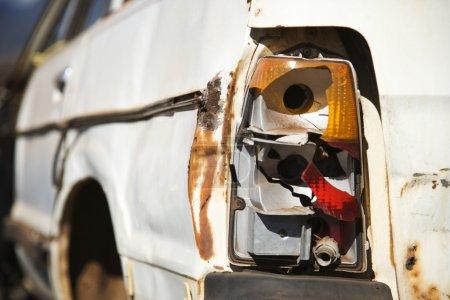 Photo pour Gros plan du feu arrière cassé à l'arrière d'une vieille voiture abandonnée et rouillée  . - image libre de droit