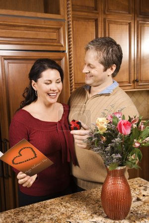 Man giving woman gifts.