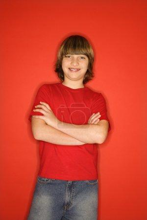 Photo pour Portrait d'un garçon caucasien en due forme studio sur fond rouge avec les bras croisés. - image libre de droit