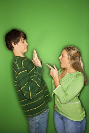 Photo for Portrait of Caucasian teen girl pointing at yelling at teen boy who is holding up hands to her against green background. - Royalty Free Image
