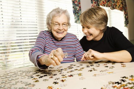 Photo for Elderly woman and a younger woman work on a jigsaw puzzle. Horizontal shot. - Royalty Free Image
