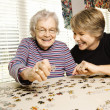 Elderly woman and a younger woman work on a jigsaw...