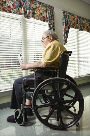 Photo for Elderly man reads a newspaper while sitting in wheelchair. Vertical shot. - Royalty Free Image