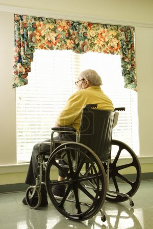 Photo for Elderly man in wheelchair sits and looks out of large window. Vertical shot. - Royalty Free Image