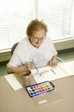 Foto de Anciana caucásica pintando con acuarelas en el centro comunitario de jubilación. - Imagen libre de derechos