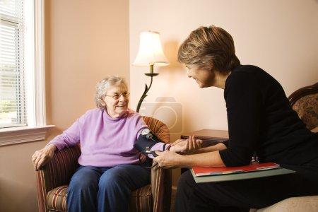 Nurse checks an elderly woman's blood pressure in ...