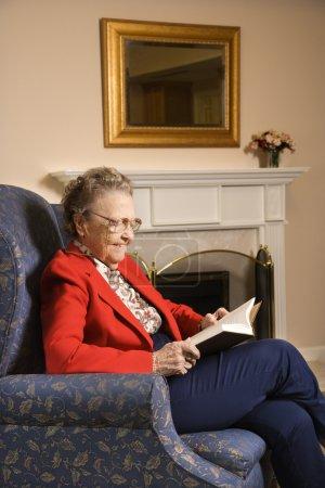 Foto de Libro de lectura caucásica anciana en silla en el centro comunitario de jubilación. - Imagen libre de derechos