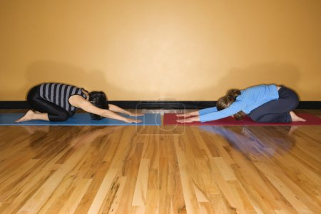 Photo for Two women kneel towards each other in child's pose yoga position at the gym. Horizontal shot. - Royalty Free Image