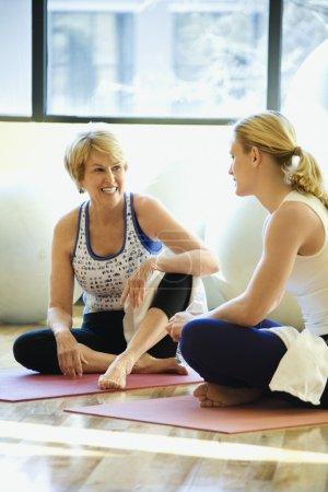 Photo pour Femmes assis sur des nattes et bénéficiant d'une conversation à la salle de gym. Il y a des ballons d'exercice derrière eux. Défroissage vertical. - image libre de droit