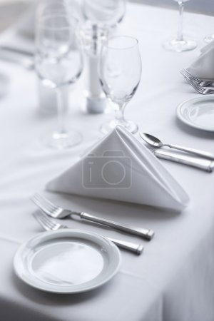 Photo for Place settings on an elegant, white dining table in a restaurant. Vertical shot. - Royalty Free Image
