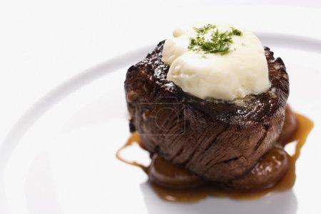 Photo pour Entrée de filet de boeuf avec garniture et sauce brune sur une assiette blanche. Plan horizontal . - image libre de droit