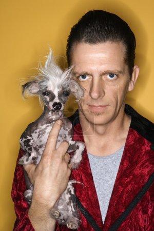 Man holding Chinese Crested dog.
